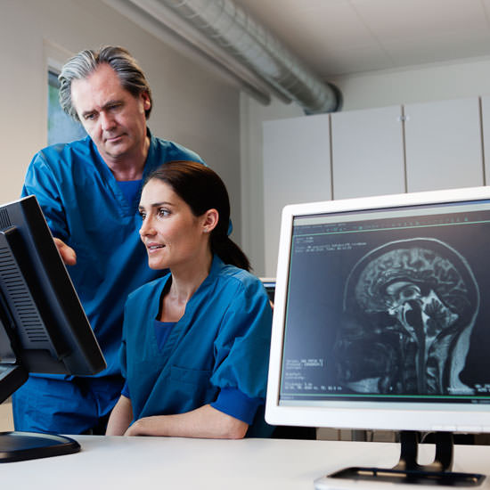 Doctor and nurse looking at computer screen with MR scan images. MR-Image of human head in foreground